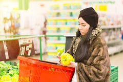 Молодая женщина при корзина для товаров выбирая болгарский перец паприки во время покупок на супермаркете женщина ног принципиаль Стоковое Изображение RF