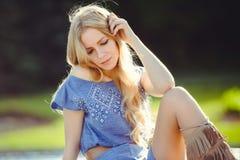 Молодая женщина при красивое белокурое прямое длинное солнце играя волосы сидя на лужайке заботливой стоковая фотография