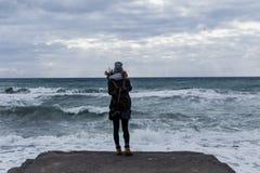 Молодая женщина при рюкзак стоя на крае ` s скалы Стоковые Изображения RF