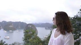 молодая женщина при солнечные очки смотря далеко на предпосылке моря и острова сток-видео