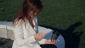 Молодая женщина при smartphone сидя в парке Фото дела моды красивой девушки в белой вскользь сюите с телефоном акции видеоматериалы
