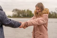 Молодая женщина пробует вытянуть ее партнера в воду стоковое фото rf