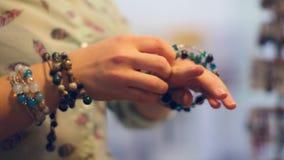 Молодая женщина пробует дальше браслеты на рынке сток-видео