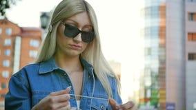 Молодая женщина пробует unravel длинный белый кабель наушников Портрет блондинкы с преподавателями точных наук в ее руках сток-видео