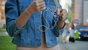 Молодая женщина пробует unravel длинный белый кабель наушников Портрет блондинкы с преподавателями точных наук в ее руках видеоматериал