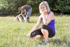 Молодая женщина пробурена пока ее партнер играет с собаками Стоковое Изображение RF