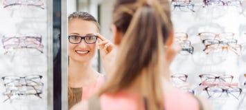 Молодая женщина пробуя модные стекла в магазине optometrist стоковые фото