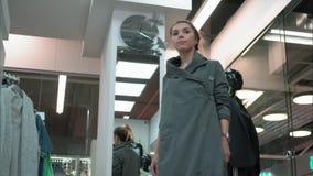 Молодая женщина пробуя на новом кардигане около зеркала в магазине акции видеоматериалы