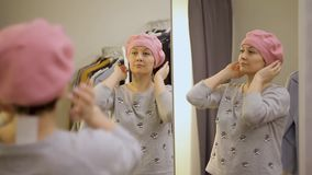 Молодая женщина пробуя на одеждах Привлекательная кавказская женщина смотрит в зеркале, поворачивающ ее голову, пробуя на шляпе в видеоматериал