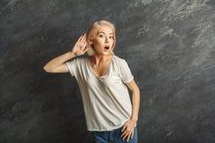 Молодая женщина пробуя слушать сплетня стоковая фотография