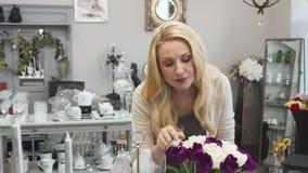 Молодая женщина проверяет свежесть цветков стоковые изображения rf