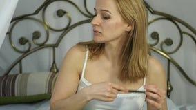 Молодая женщина просыпает вверх и расчесывающ ее волосы на кровати движение медленное сток-видео