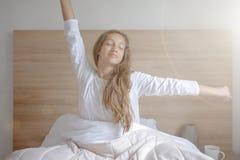 Молодая женщина просыпая вверх в ее спальне, сидя на кровати протягивая оружия стоковая фотография rf