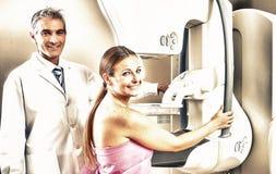 Молодая женщина проходя маммографию с наблюдением доктора стоковая фотография