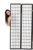 Молодая женщина пряча за панелью стоковая фотография