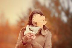 Молодая женщина прячет сторону с разрешением клена желтого цвета осени Стоковое фото RF