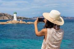 Молодая женщина путешественника делая фото с камерой мобильного телефона li стоковая фотография rf