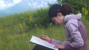 Молодая женщина путешественника ища направление с компасом на предпосылке карты в горах видеоматериал