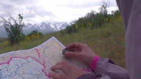 Молодая женщина путешественника ища направление с компасом на предпосылке карты в горах сток-видео