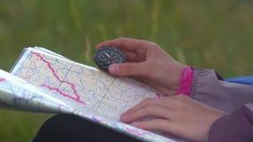 Молодая женщина путешественника ища направление с компасом на предпосылке карты в горах акции видеоматериалы
