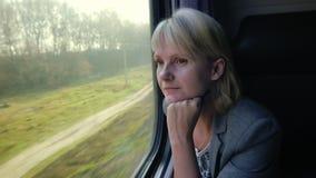Молодая женщина путешествует поездом, смотрит вне окно на красивом пейзаже, мечтах акции видеоматериалы
