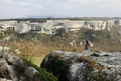 Молодая женщина путешествуя в горах, городах пещеры, пешем туризме, идя в горы стоковое фото