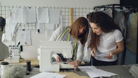 Молодая женщина работает с швейной машиной и проверяет стежки когда ее коллега придет к ей с эскизом Женщины сток-видео