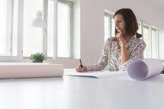 Молодая женщина работая в ее офисе стоковые изображения