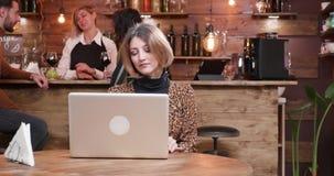 Молодая женщина работая в занятой кофейне сток-видео