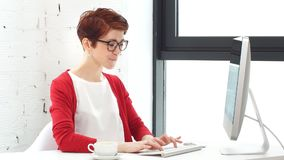 Молодая женщина работая в офисе, сидя на столе, используя компьютер и смотря на экране акции видеоматериалы