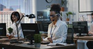 Молодая женщина работая на ее столе
