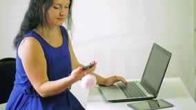 Молодая женщина работая на компьтер-книжке и отвечая телефонному звонку Камера двигает снизу вверх видеоматериал