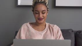 Молодая женщина работая на ноутбуке и усмехаясь на софе дома акции видеоматериалы