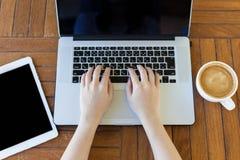 Молодая женщина работая на портативном компьютере помещенном на деревянном столе Взгляд сверху Стоковое фото RF