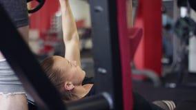 Молодая женщина работая со штангой на стенде в спортзале видеоматериал