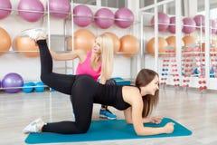 Молодая женщина работая с ее инструктором фитнеса Стоковая Фотография RF