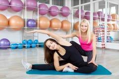 Молодая женщина работая с ее инструктором фитнеса Стоковое Изображение