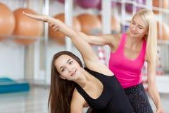 Молодая женщина работая с ее инструктором фитнеса Стоковые Изображения RF