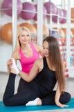 Молодая женщина работая с ее инструктором фитнеса Стоковые Фото