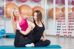 Молодая женщина работая с ее инструктором фитнеса Стоковая Фотография