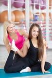 Молодая женщина работая с ее инструктором фитнеса Стоковые Фотографии RF