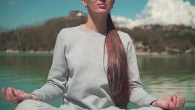 Молодая женщина размышляет в солнце пока сидящ на деревянной пристани озера на весенний день, ослабляя в природе видеоматериал