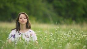 Молодая женщина размышляя в высокой зеленой траве, единстве с природой, останавливает думать акции видеоматериалы