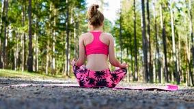 Молодая женщина размышляя в йоге положения лотоса практикуя в лесе Стоковое Изображение