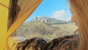 Молодая женщина раскрывает вход шатра Взгляды украдкой девушки из шатра сь природа Отключение к сельской местности Любопытное акции видеоматериалы