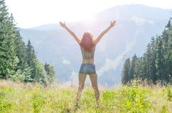 Молодая женщина раскрывает ее руки на верхней части горы, свободном s Стоковая Фотография RF