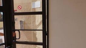Молодая женщина раскрывает заднюю дверь нося красное платье и шляпу Задняя дверь открытая изнутри ( видеоматериал