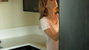 Молодая женщина раскрывает холодильник, выбирает продукты E акции видеоматериалы