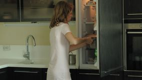 Молодая женщина раскрывает холодильник, выбирает продукты E сток-видео