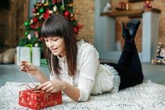 Молодая женщина распаковывает подарочную коробку Новый Год концепции, с Рождеством Христовым, Стоковые Изображения RF